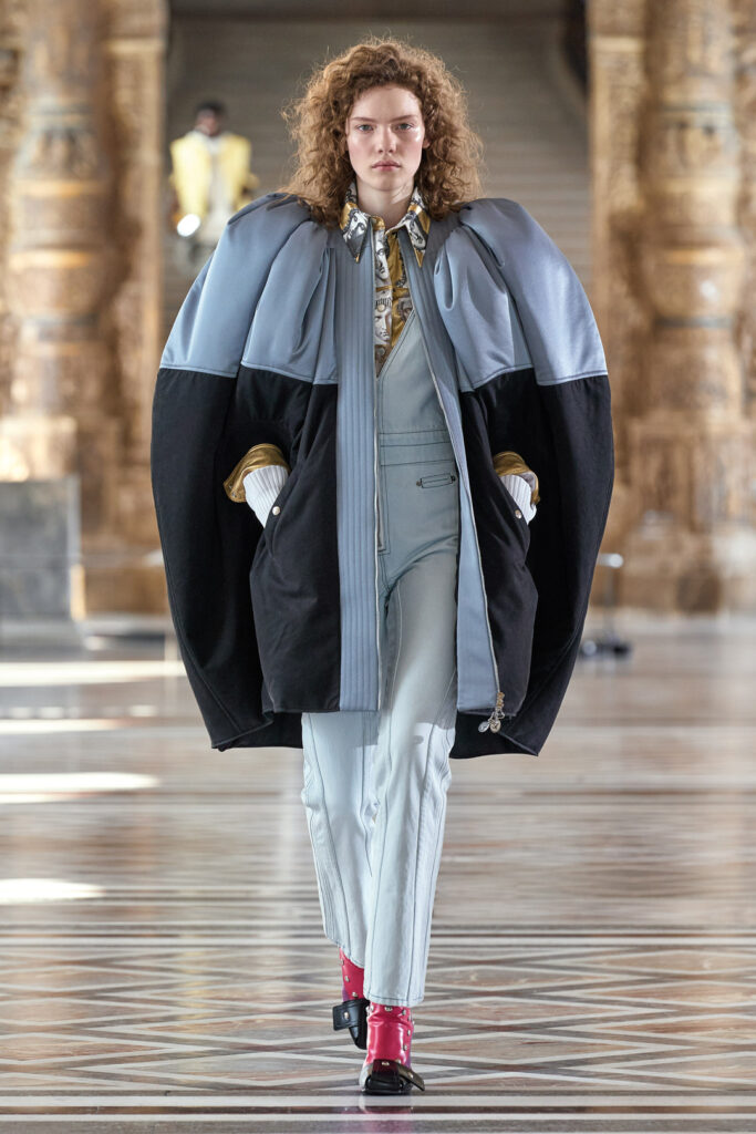 FW2021 Louis Vuitton poncho bears gentle curves in its rounded cocoon shape that encase the wearer like a comforting bear hug, while its dusky pastel-blue and black colourblocking adds visual interest
